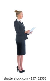 Side view of cute blonde businesswoman working with her tablet on white background