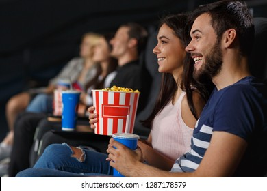 Side view of cute couple having date and watching funny movie at cinema. Young girl and man sitting together, eating popcorn and laughing at new comedy. Concept of happiness and entertainment.