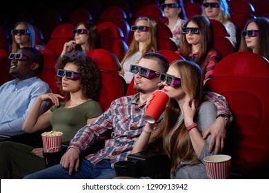 Side view of cute couple having date and watching movie in 3d at cinema. Young girl and man sitting together and embracing, eating popcorn watching comedy. Concept of entertainment.
