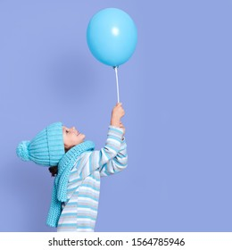 Side view of cute little girl holding balloon in hands, looking up on her toy, wearing striped turtleneck, cap and scarf in turquoise colour, female child posing isolated over purple studio background