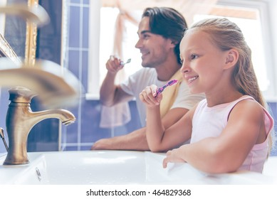 Side view of cute little girl and her handsome father are looking through the mirror and smiling while brushing teeth in bathroom at home