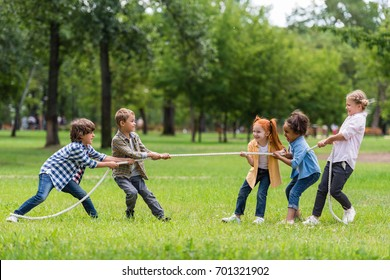 side view of cute little multiethnic children pulling rope in park