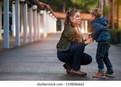 Side view - cute mother and son embrace while walking on an asphalt road on a warm autumn day
