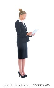Side view of cute young businesswoman using her tablet on white background