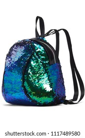 Side view of a dark blue, green and black mermaid scale backpack isolated against the white background. The fashionable lady's accessory featuring iridescent sequins, a top handle, a zipper closure.