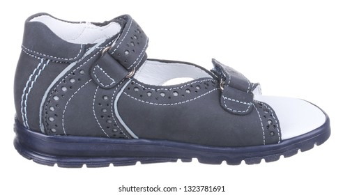 Side view of dark blue and white suede boy sandal with perforation, slits and slots, and two velcros, isolated on white