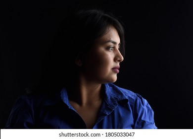side view of dark portrait of a latin woman on black background, serious
