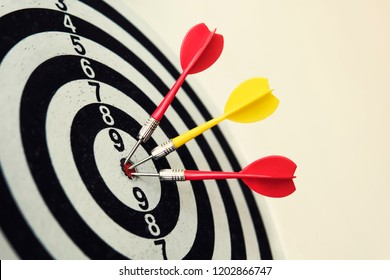 Side view of a dartboard with three darts in the bull's eye. Well-aimed dart throwing. Triple bull's-eye hit. Three well-made dart throws. Successful attempts. To attempt difficult task. Darts ace