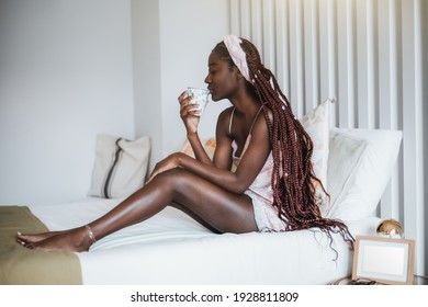 Side view of a dazzling young black female with long braided hair, in a nightie, sitting on a white neatly made bed of a bedroom after waking up and drinking a hot delicious tea from the cup