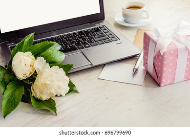 Side view of a deck with computer, bouquet of peonies flowers, cup of coffee, empty card and pink dotted gift box. White rustic wooden background. Romantic and feminine outlook.