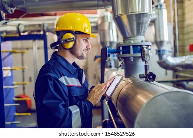 Side view of dedicated factory worker standing next to boiler and holding tablet. Worker is dressed in protective uniform, having hardhat and antiphons.