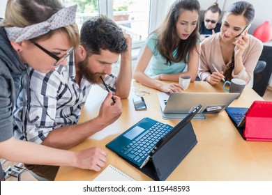 Side view of a dedicated self-employed young man analyzing a difficult task while working in a modern hub for digital nomads or independent contractors
