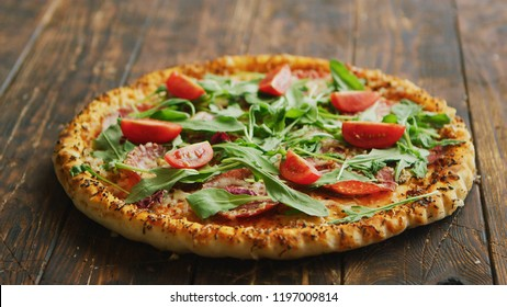 Side view of delicious italian pizza served on dark brown wooden table with copy space