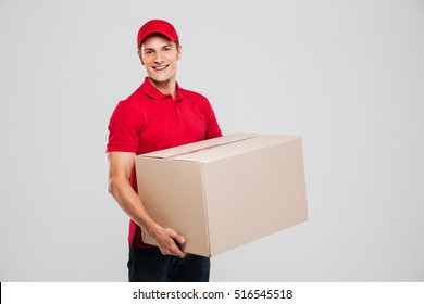 Side view of delivery man with box in studio. isolated gray background