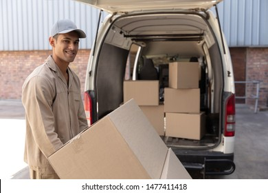 Side view of delivery man carrying cardboard boxes on trolley near van outside the warehouse. This is a freight transportation and distribution warehouse. Industrial and industrial workers concept