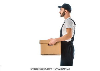 side view of delivery man in overalls and cap holding cardboard box isolated on white