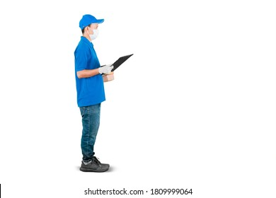Side view of delivery man wearing face mask and gloves while holding packages and clipboard in the studio. Isolated on white background