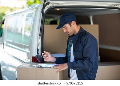 Side view of delivery person writing in clipboard while standing by van
