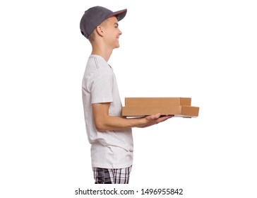 Side view of Delivery teen boy in cap holding cardboard box with pizza. Happy child courier - profile, isolated on white background. Cute smiling teenager with fresh pizza in box. Guy looking away.