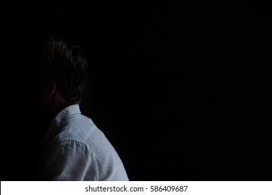 Side view of depressed man in black interior