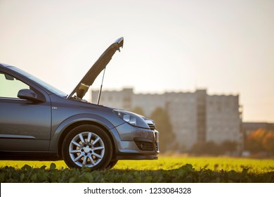 Side view detail of car with open hood on empty gravel field road on blurred apartment building and clear bright sky copy space background. Transportation, vehicles problems and breakdowns concept.