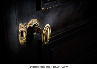 side view detail of vintage antique golden door know with metallic carvings and keyhole on dark background natural lightning
