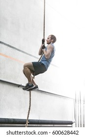 Side view of determined man climbing rope in gym