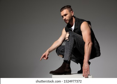 Side view of a determined young man pointing and looking forward while squatting on a chair and wearing a black jeans vest on gray studio background