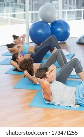 Side view of determined young people doing sit ups in the fitness studio
