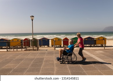 Side view of disabled senior man being pushed on wheelchair by senior woman at beach on a sunny day