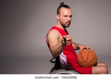side view of disabled sportsman in wheelchair holding basketball ball and pointing at camera