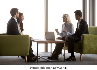 Side view diverse businesspeople negotiating sitting near panoramic window on couch in modern cozy office. Middle aged ceo talking with asian caucasian and middle eastern ethnicity partners or interns