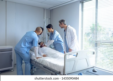 Side view of diverse doctors examining Asian female patient in bed in ward at hospital. Patient is wearing oxygen mask.