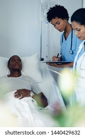 Side view of diverse female doctors checking African-American male patient in the ward at hospital