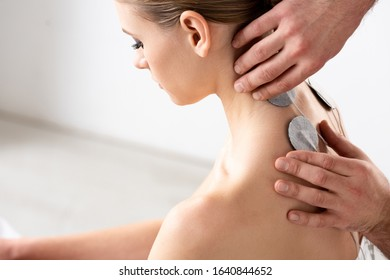 Side view of doctor setting electrodes on patient neck during electrode treatment in clinic