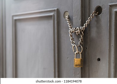A side view of a door locked with chains and a padlock. Building and security as a concept
