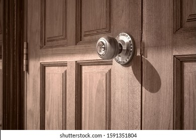 Side view of doorknob on wooden door in monochrome style, home exterior architecture concept