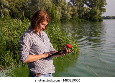 side view of ecologist entering data on green algae taken in river on tablet