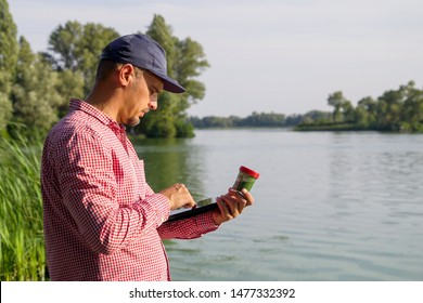 side view of ecologist on river bank entering data on green algae on tablet
