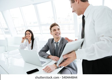 Side view of Elderly business man showing tablet computer to his colleagues on conference