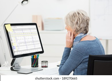 Side view of an elderly businesswoman working at her desk in the office studying a spreadsheet on a large desktop monitor