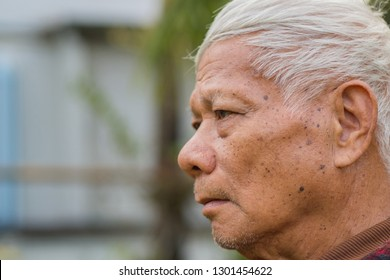 Side view of elderly man face worried and  looking away to side on nature background. Space for text. Selective focus