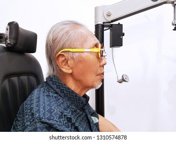 Side view of elderly man using a glasses phoropter while checking his myopic eyes at ophthalmologist