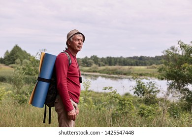 Side view of eldery man with backpack and blue rug, enjoying of admiring majestic view of river while walking in wonderful countryside during his active vacation. Traveling and backpacking concept.