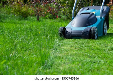Side view of an electric lawn mower standing on a trimmed lawn