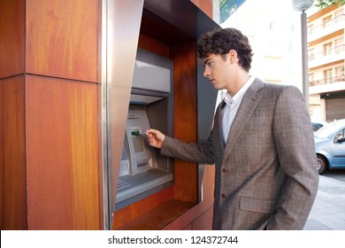 Side view of an elegant businessman withdrawing money from a wood decorated bank cash point, outdoors.