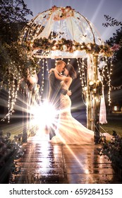 Side view of elegant couple embracing in illuminated gazebo at night