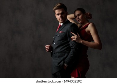 side view of a  elegant couple where the man is standing with one hand in his pocket,looking down in front of his woman who holds his arm and raises her hand behind her head on gray studio background