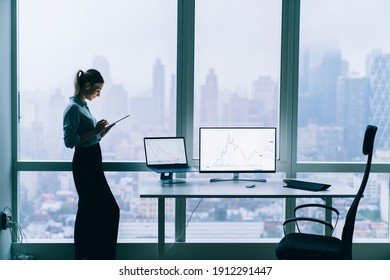 Side view of elegant female analyzing charts on gadgets and concentrating on screen of tablet while standing near full wall window in modern office