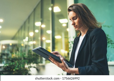 side view of an elegant girl in a business black suit who is holding a tablet and reading correspondence,  financial adviser uses Internet technology on a pc computer near the office